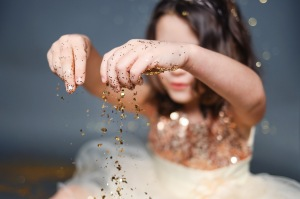 close up of little girl wearing dress playing with gold glitter