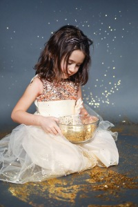 little girl wearing dress holding glass bowl filled with gold glitter
